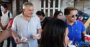John and Angie distribute lunch boxes to children